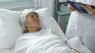 Tilt up of cheerful senior woman lying in hospital bed and talking with female Asian doctor in lab coat making notes on clipboard; name Kim Sang Mi is used in fictitious manner