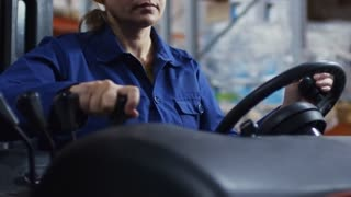 Tilt up of concentrated female worker wearing blue overalls and hard hat operating forklift factory warehouse