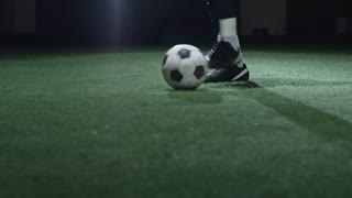 Tilt up of concentrated soccer player juggling ball on field in dark stadium with projector lightning in background