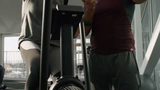 Tilt up of elderly male fitness trainer looking at wristwatch and talking to cheerful senior woman training on cycling machine in gym