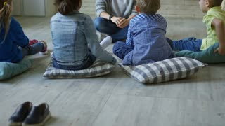 Tilt up of group of little children sitting on the floor in kindergarten classroom and listening to young female teacher