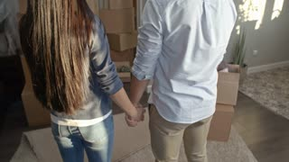 Tilt up of happy Asian couple holding hands and looking at pile of cardboard boxes stacked in living room of their new house, then hugging and smiling with excitement