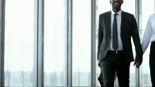 Tilt up of happy black businessman in suit and smiling businesswoman in formalwear holding hands and walking along hallway of office building with panoramic windows