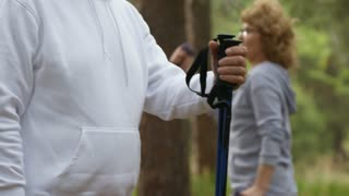 Tilt up of happy elderly man with trekking poles looking at camera and smiling while posing in park; senior woman in glasses exercising in background