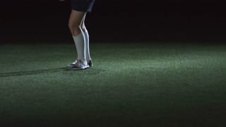 Tilt up of junior soccer player shooting a ball and falling down on artificial turf in indoor arena in low key lightning
