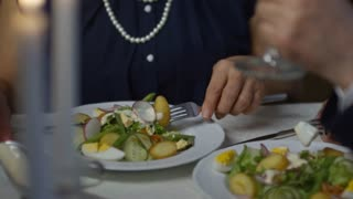 Tilt up of laughing senior woman eating salad and drinking wine while chatting with unrecognizable date in restaurant