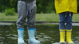 Tilt up of little boy and girl in yellow raincoat and rubber boots holding origami paper boats and standing in puddle