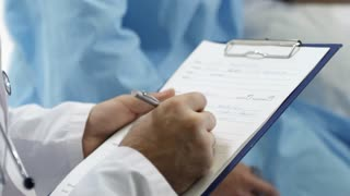 Tilt up of male doctor filling diagnosis form and talking with female patient