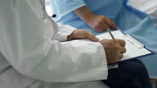 Tilt up of male doctor in lab coat filing patient form on clipboard while talking with Asian woman sitting on hospital bed