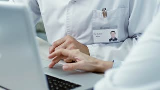 Tilt up of mature male doctor nodding and listening to his talking female colleague with laptop; name on badge is used in fictitious manner
