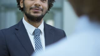 Tilt up of middle eastern entrepreneur in formal suit talking to business partners