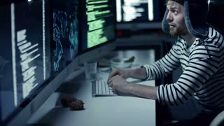 Tilt up of Russian hacker in fur ear flap hat and sailor shirt hacking information in office at night. Man working on computer with multiple monitors, projector lightning in background