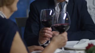 Tilt up of senior man and woman clinking glasses and drinking wine during romantic date in restaurant