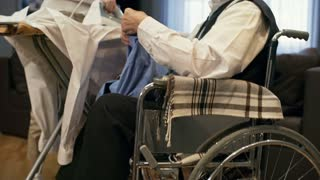 Tilt up of senior man in wheelchair giving shirt to cheerful young social worker ironing clothes in living room
