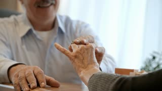 Tilt up of senior man putting diamond ring on finger of elderly lady while making a proposal to her at restaurant date