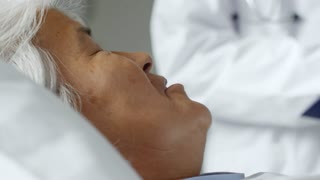 Tilt up of senior patient lying in hospital bed and talking with cheerful Asian doctor in lab coat