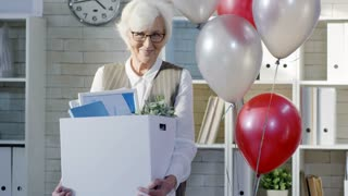 Tilt up of shot retiring happy senior woman standing at her office desk decorate with air balloons and holding box with her belongings