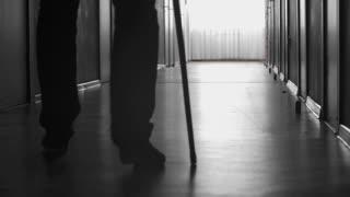 Tilt up of silhouette of man with limp walking along dark corridor using stick