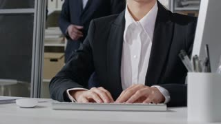 Tilt up of smart businesswoman in eyeglasses and formal suit typing on computer at desk while two business partners shaking hands in background in office