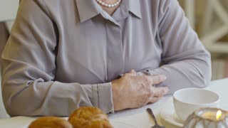 Tilt up of smartly dressed elderly woman smiling and looking into camera