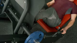 Tilt up of strong elderly man with grey hair training on leg press machine in gym