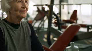 Tilt up of tired elderly woman with grey hair drinking from sports water bottle after workout in gym