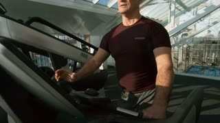 Tilt up of tired senior man with fit body and grey hair walking on treadmill and drinking water while training in gym