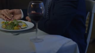 Tilt up of unrecognizable elderly man gifting ring and making proposal to happy senior woman during romantic date in restaurant