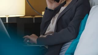 Tilt up of young Asian businesswoman using laptop and chatting on phone while sitting on comfortable bed in hotel room
