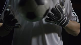 Tilt up of young handsome goalkeeper in gloves juggling soccer ball with hands and looking at camera in dark arena