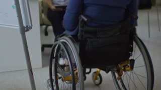 Tilt up rear view of businesswoman in wheelchair sitting in front of colleagues in the office, explaining something on flipchart and answering questions during corporate training