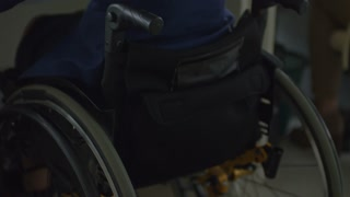 Tilt up rear view of disabled businesswoman on wheelchair working on computer at office desk