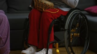 Tilt up shot of beautiful paraplegic woman in wheelchair playing ethnic drums as bearded man singing and playing guitar at home