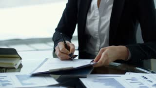 Tilt up shot of cheerful businesswoman signing document and shaking hands with black businessman on meeting