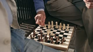 Tilt up shot of chessboard and old man playing chess with his friend on bench in pedestrian street