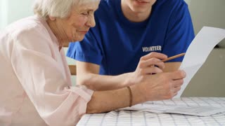 Tilt up shot of elderly lady holding document and trying to read it while young male caregiver sitting next to her and helping her