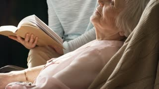 Tilt up shot of elderly lady relaxing in rocking chair and listening to young female caregiver who is reading book aloud to her in the background