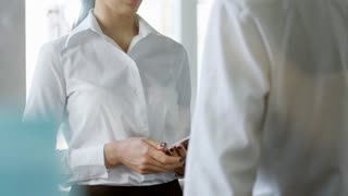 Tilt up shot of friendly young woman discussing work with potential business partner seen from his back