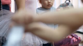Tilt up shot of little girl standing in dressing room in dance studio and waiting for her mother to finish making ballet bun