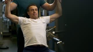 Tilt up shot of middle-aged sportsman performing seated overhead shoulder press with dumbbells under guidance of trainer