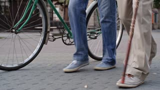 Tilt up shot of senior friends walking together along pedestrian street and talking to each other, one with walking stick and one with bicycle