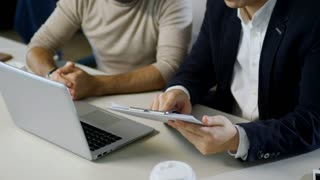 Tilt up shot of two Asian men using laptop computer when discussing work, one of them drinking coffee