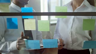 Tilt up shot of two office workers of different ethnicities standing by glass wall and discussing ideas written on sticky notes