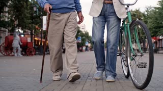 Tilt up shot of two senior men, one with walking stick and one with bicycle, walking along pedestrian street and having friendly conversation