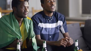 Tilt up shot of two young African-American men sitting on couch with flag of Brazil, watching soccer on TV, yelling, hugging and celebrating goal