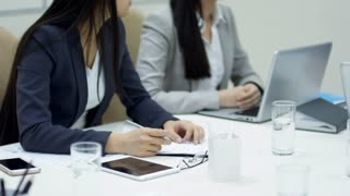 Tilt up shot of two young Asian women talking to male boss when sitting at desk in conference room during meeting