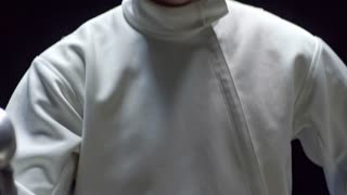 Tilt up shot of young man in white costume holding fencing foil and putting protective mask in slow motion