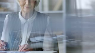 Tilt up shot through glass window in office: elderly businesswoman with grey hair sitting at her desk and smiling for camera