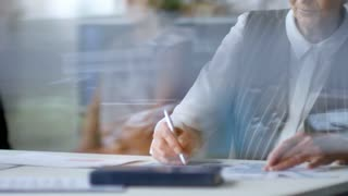 Tilt up shot through glass window in office: senior businesswoman with grey hair sitting at her desk and working with documents