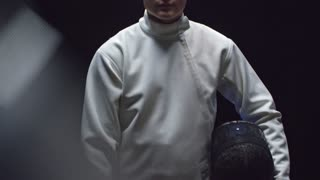 Tilt up studio shot of young professional fencer in white costume moving sword towards the camera and putting protective mask in slow motion